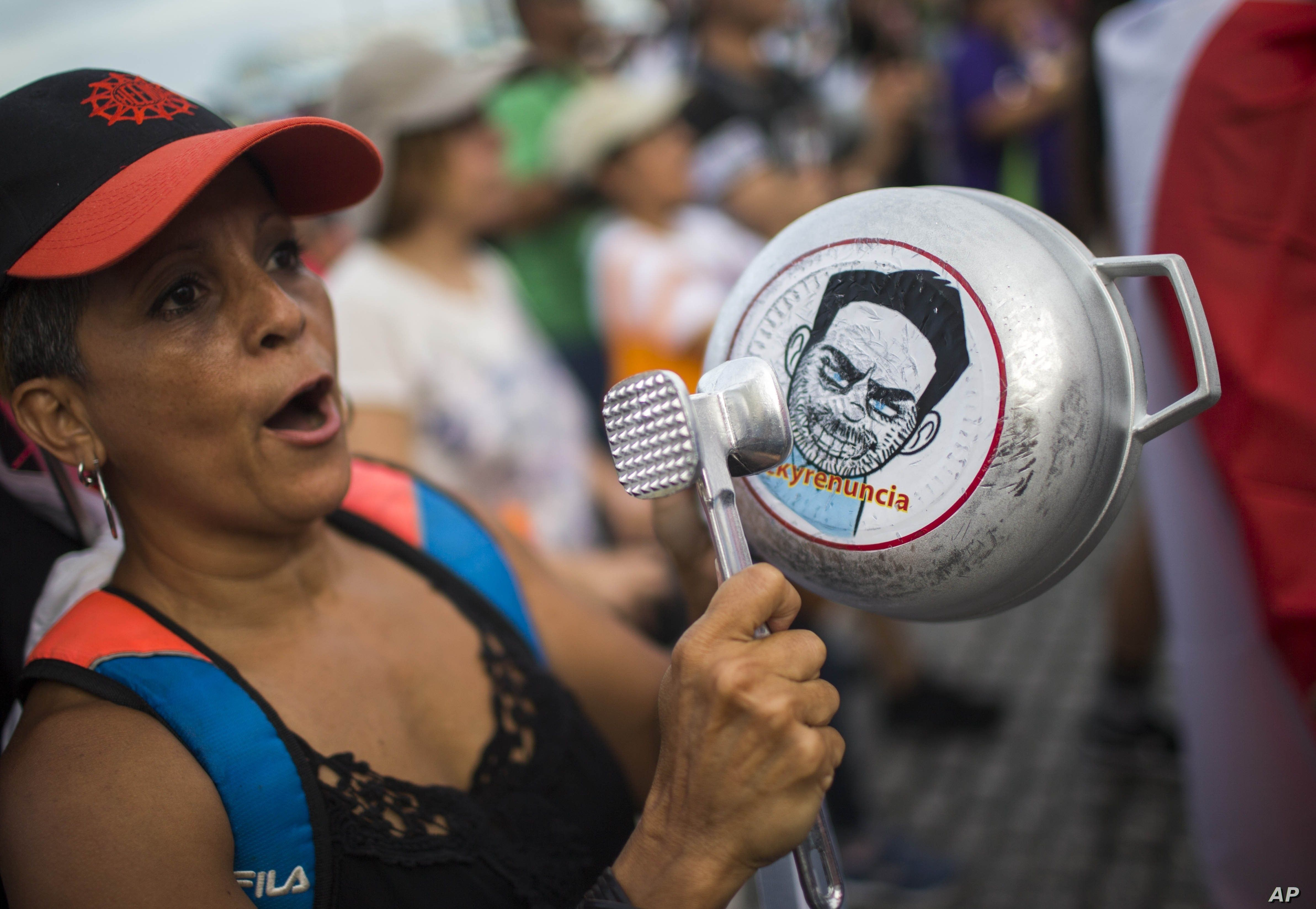 FILE - A demonstrator bangs on a pot that has a cartoon drawing of Governor Ricardo Rossello and text the reads in Spanish
