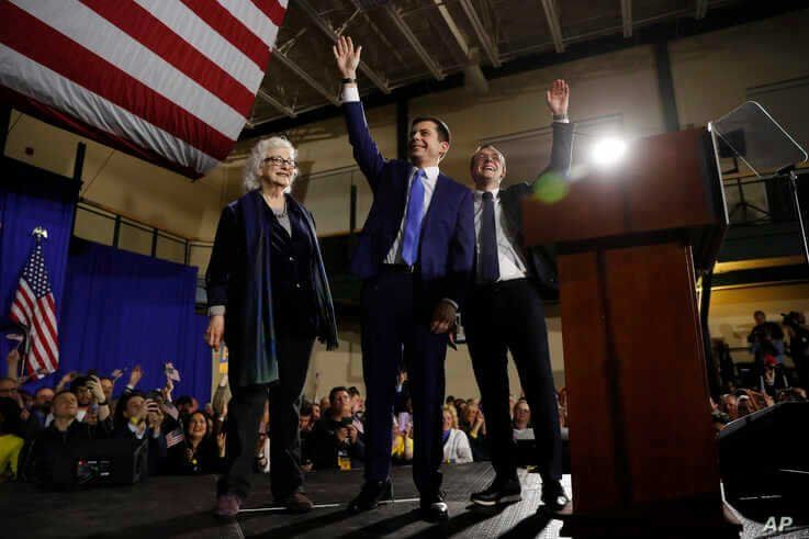 Democratic presidential candidate former South Bend, Ind., Mayor Pete Buttigieg, center, his husband Chasten Buttigieg, right,…