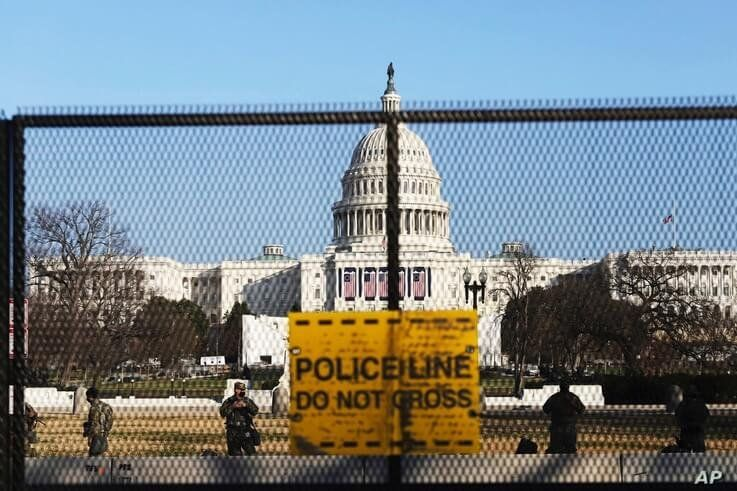 National guards are seen Wednesday, Jan. 13, 2021 on a fence that was erected to reinforce security at the Capitol in…