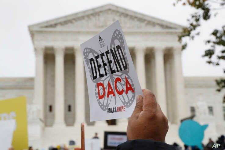 FILE - In this Nov. 12, 2019, file photo people rally outside the Supreme Court as oral arguments are heard in the case of…