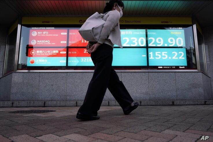 A woman walks past an electronic stock board showing Japan's Nikkei 225 index at a securities firm in Tokyo Friday, Oct. 2,…