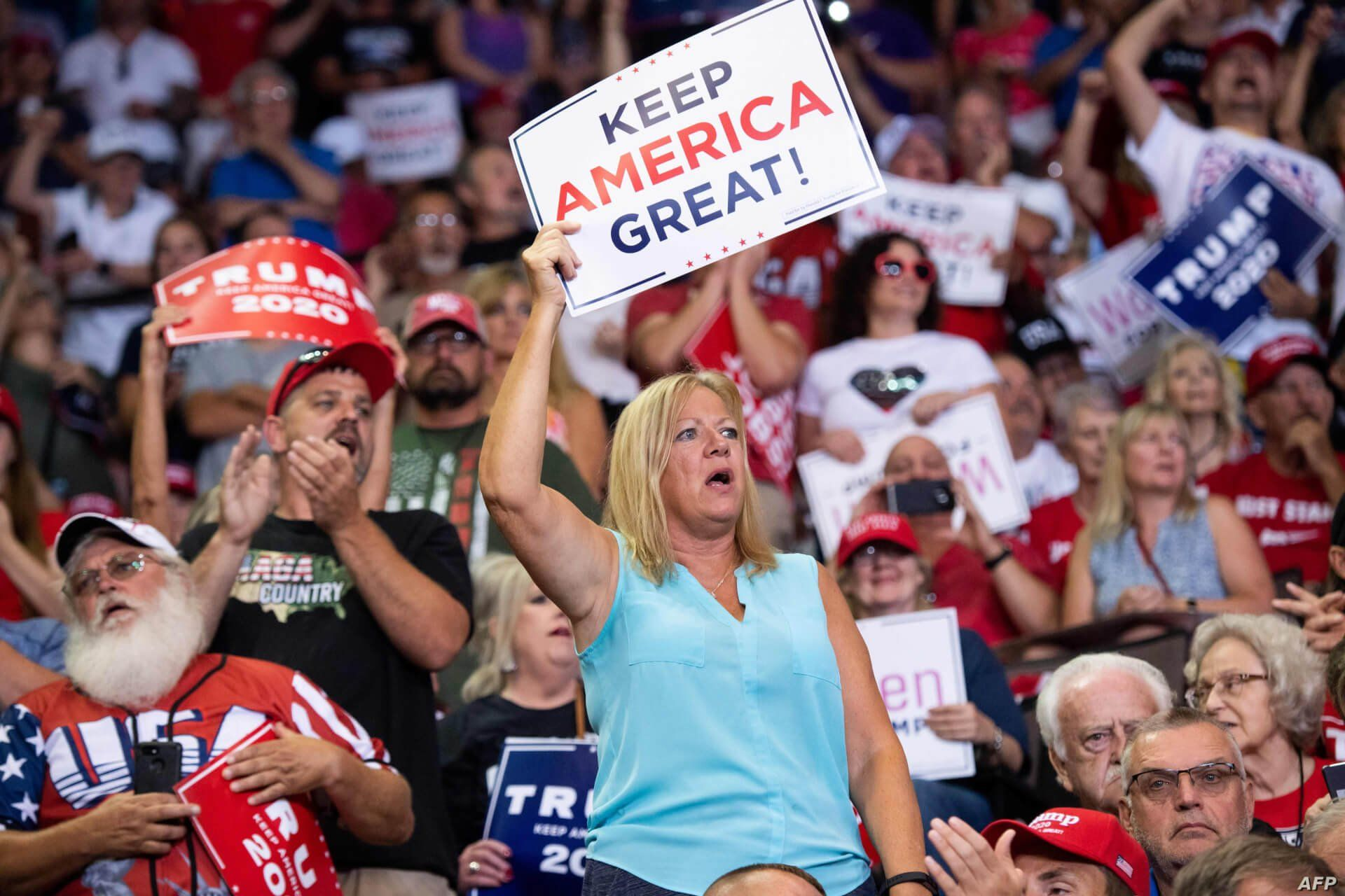 Supporters cheer as US President Donald Trump holds a