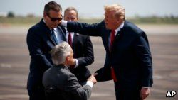 President Donald Trump talks with Sen. Ted Cruz, R-Texas, left, and Gov. Greg Abbott, R-Texas, after arriving at Ellington Field Joint Reserve Base, May 31, 2018, in Houston.