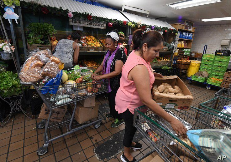 People on low-incomes and retirees choose food at the World Harvest Food Bank after the announcement that the Trump…
