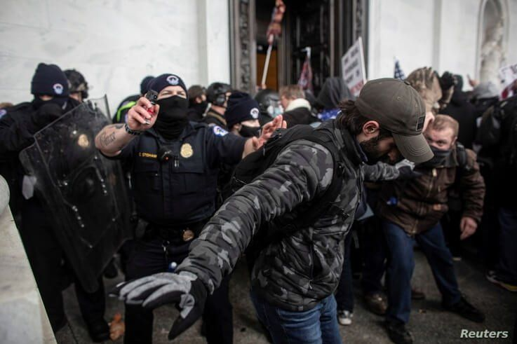 Members of law enforcement clash with pro-Trump protesters as they storm the U.S. Capitol during a rally to contest the…