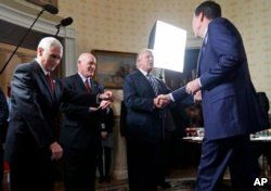 FILE - Pesident Donald Trump shakes hands with then-FBI Director James Comey in the Blue Room of the White House, in Washington, Jan. 22, 2017.