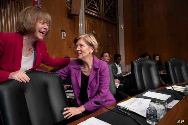 Sen. Tina Smith, D-Minn., left, speaks with Sen. Elizabeth Warren, D-Mass., at the start of a Senate hearing with healthcare…
