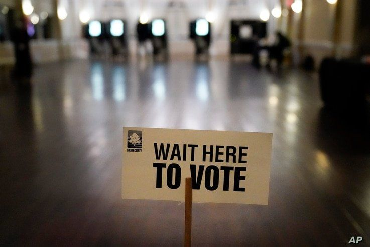 A sign is displayed for voters to guide the way at a precinct during Georgia's Senate runoff elections on Tuesday, Jan. 5, 2021…