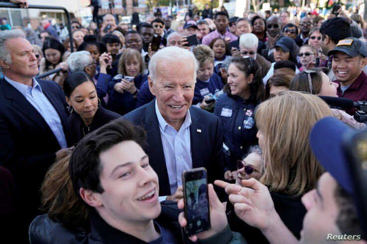 Democratic presidential candidate and former Vice President Joe Biden takes selfies with supporters at a