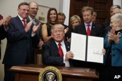 President Donald Trump shows an executive order on health care that he signed Oct. 12, 2017. The Trump administration says it's freezing payments under an 'Obamacare' program that protects insurers with sicker patients from financial losses, a move expected to add to premium increases next year.