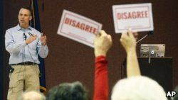 """Audience members hold signs reading """"DISAGREE"""" as U.S. Rep. Scott Perry, R-Pa., speaks during a town hall meeting, March 18, 2017, in Red Lion, Pa. Perry's event turned contentious in his conservative south-central Pennsylvania district over questions about his support for President Donald Trump's budget proposal and immigration plans and for undoing former President Barack Obama's signature health care law."""