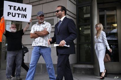 Former Donald Trump presidential campaign adviser George Papadopoulos, center, who triggered the Russia investigation and who pleaded guilty to one count of making false statements to the FBI, leaves federal court with wife Simona Mangiante, right, a