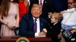"""President Donald Trump hugs Jordan McLinn, a Duchenne muscular dystrophy patient, after signing """"right to try"""" legislation in the South Court Auditorium on the White House campus, May 30, 2018, in Washington."""