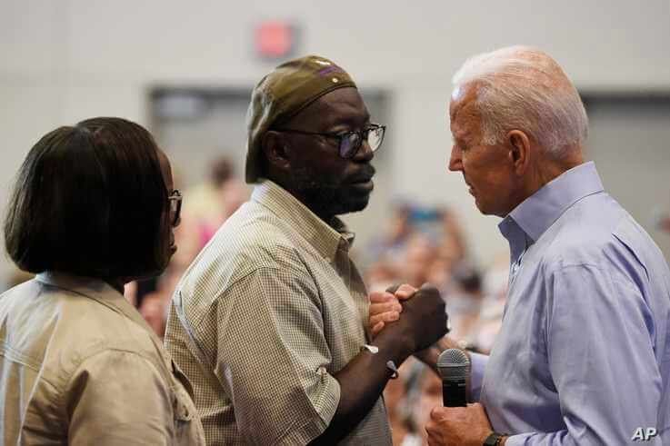 FILE - In this July 7, 2019, file photo, Democratic presidential candidate former Vice President Joe Biden, right, hold hands…