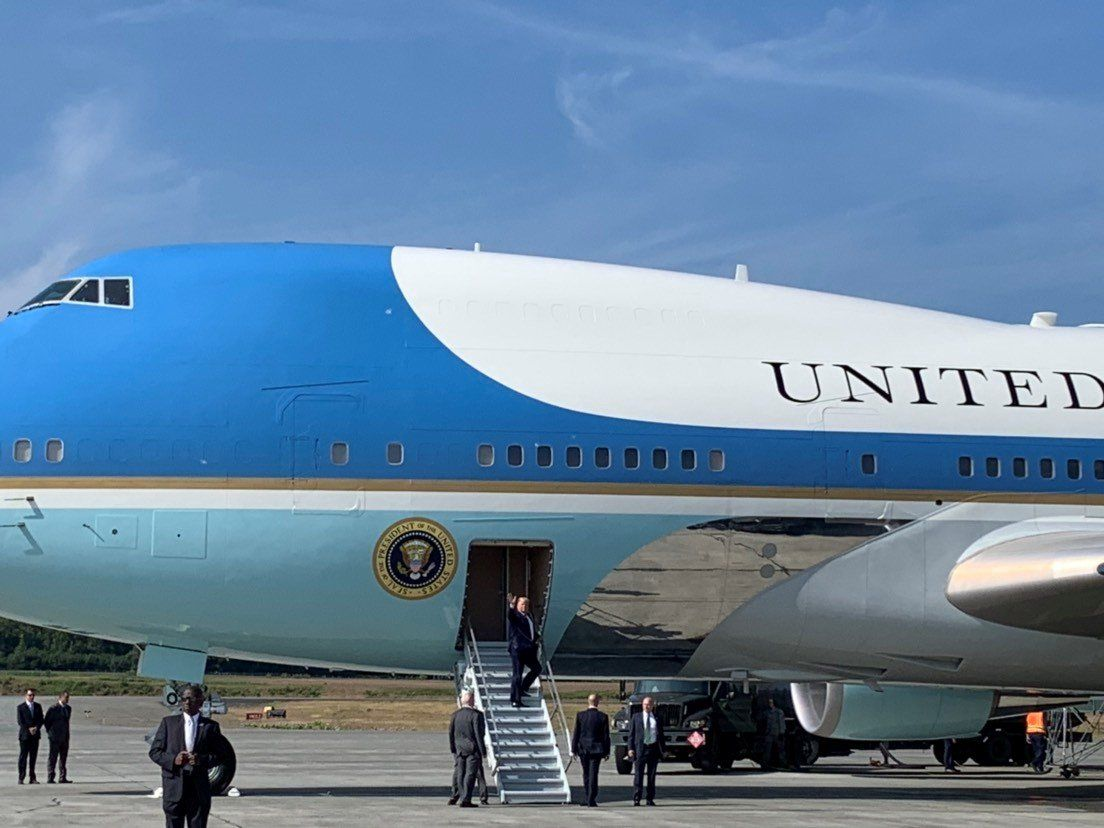 President Donald Trump, center, reboards Air Force One, after it stopped at Elmendorf Air Force Base near Anchorage, Alaska, on his way to the Group of 20 summit in Osaka, Japan, June 26, 2019.