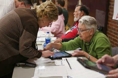 Volunteers register caucusers at a caucus site at Sparks High School for the Nevada Democratic presidential caucuses in Reno,…