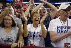 FILE - Supporters of President Donald Trump, wearing Mike Braun for Congress shirts, cheer as he arrives for a campaign rally at the Ford Center in Evansville, Ind., Aug. 30, 2018.