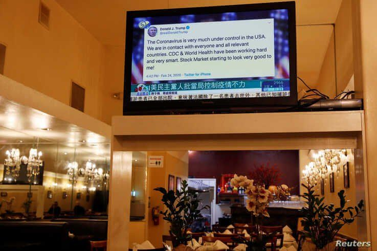 FILE - A tweet by U.S. President Donald Trump about the coronavirus is seen on a Chinese television broadcast inside a restaurant in the Chinatown section of San Francisco, California, Feb. 24, 2020. Trump tweeted before markets fell due to virus fears.