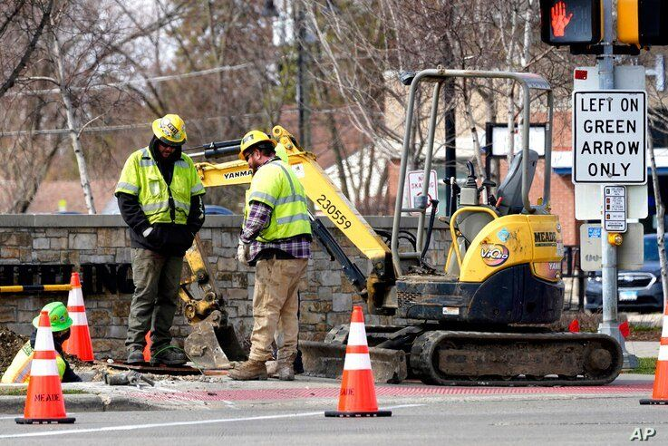 Construction workers work in Wheeling, Ill., Wednesday, March 31, 2021. President Joe Biden will unveil his $2 trillion…
