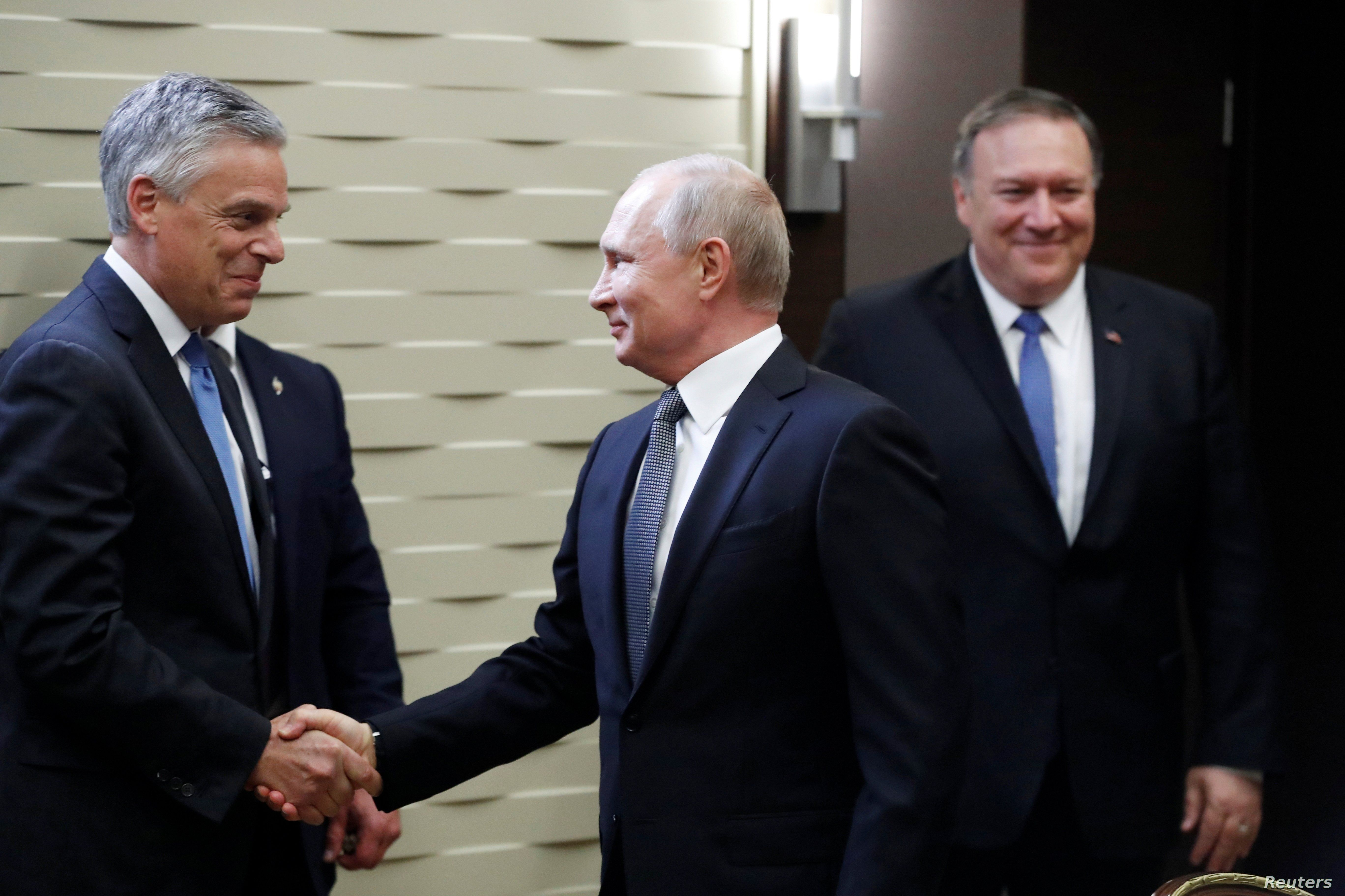 Russian President Vladimir Putin shakes hands with U.S. Ambassador to Russia Jon Huntsman, left, as U.S. Secretary of State Mike Pompeo stands behind prior to their talks in the Black Sea resort city of Sochi, May 14, 2019.