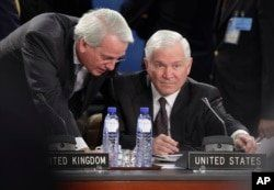 Defense Secretary Robert Gates, right, and U.S. NATO ambassador Ivo H. Daalder, talk as they prepare for a roundtable meeting of NATO defense ministers at NATO headquarters in Brussels, Oct. 14, 2010.