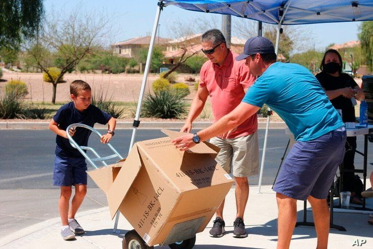 Dylan Pfeifer uses a lift to move a box filled with donated canned and boxed foods to his home in Chandler, Ariz., Saturday,…