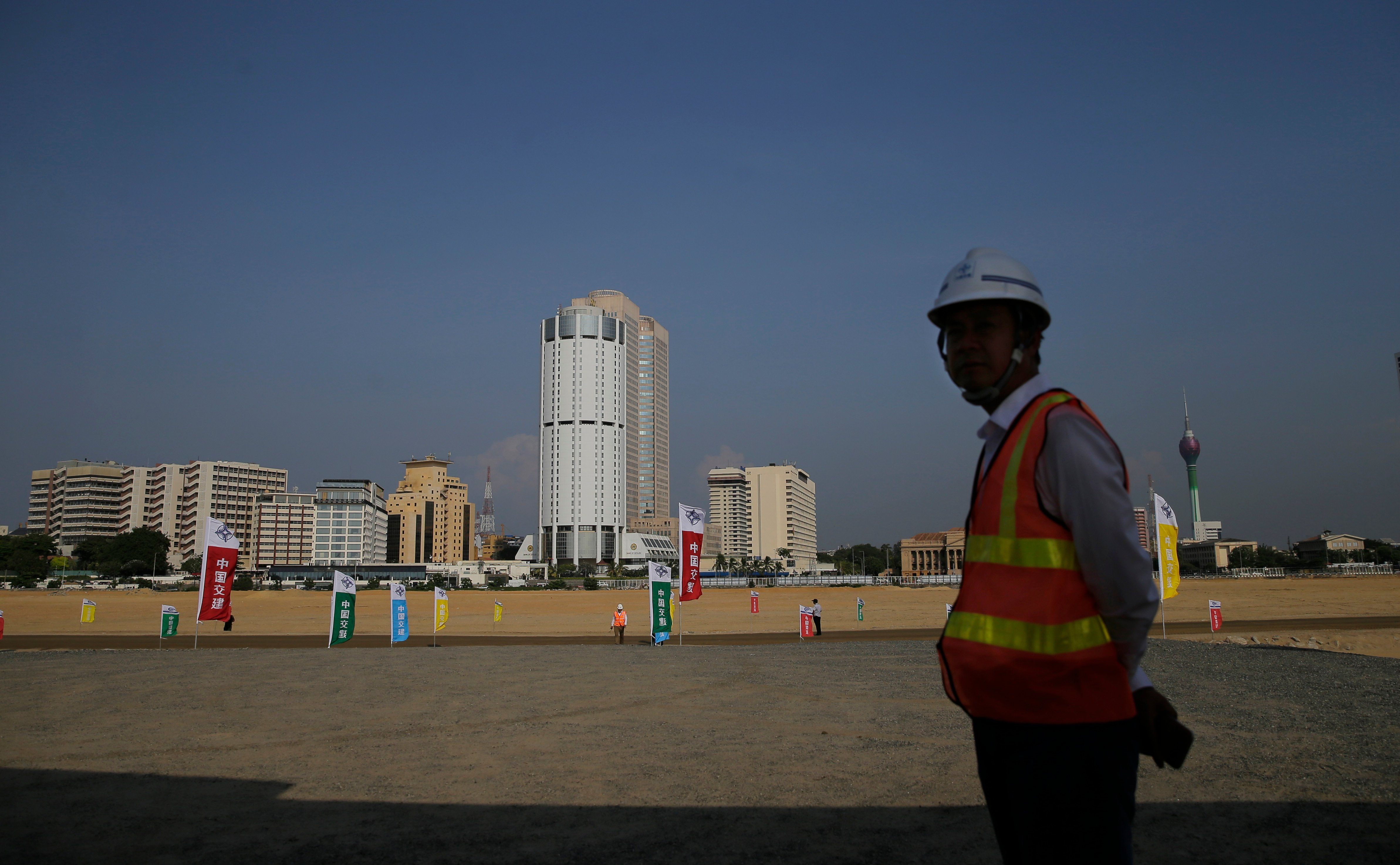 FILE - A Chinese construction worker stands on land that was reclaimed from the Indian Ocean for the Colombo Port City project, part of China's One Belt One Road initiative, in Colombo, Sri Lanka, Jan. 2, 2018.