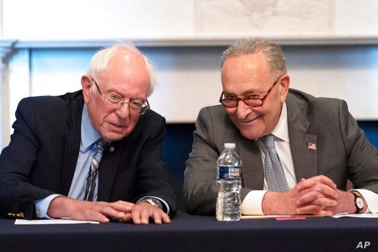 Senate Majority Leader Chuck Schumer of N.Y., right, sits next to Sen. Bernie Sanders, I-Vt., during a meeting with Senate…